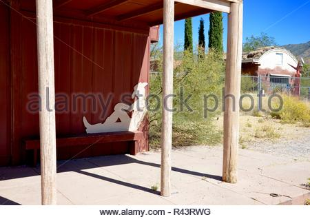 A former saloon in the small town of Chloride in Arizona, a cowboy carved from wood in front, desert landscape, summer - Stock Photo
