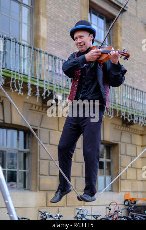 A cambridge street entertainer plays the violin whilst walking a slackline in the Market Place Cambridge, United Kingdom. - Stock Photo