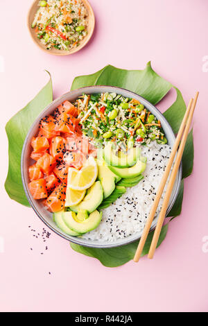 Tasty appetizing poke bowl served with salmon, avocado, rice, salad with edamame. Pink background. View from above. - Stock Photo