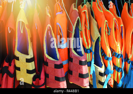 life jackets on clothes hanger / colorful of life jackets safety equipment hanging on boat - Stock Photo