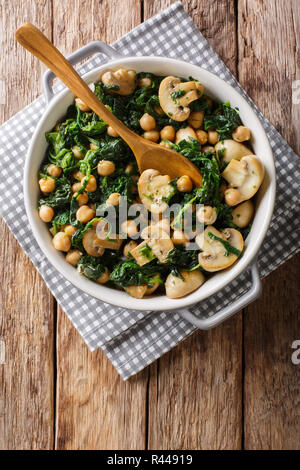 Stew of chickpeas with spinach and mushrooms close-up in a bowl on the table. Vertical top view from above - Stock Photo