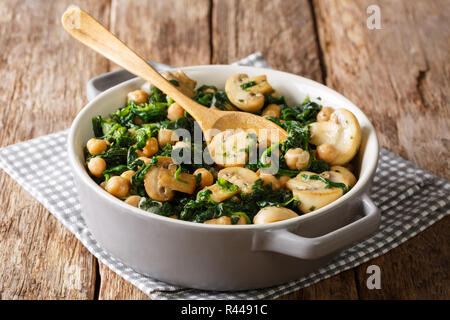 Stewed chickpea salad with spinach and champignons close-up in a bowl on the table. horizontal - Stock Photo