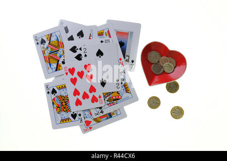 Pile of traditional playing cards on white background with Ace of Hearts shaped trinket bowl to the side with loose change in and beside it. - Stock Photo