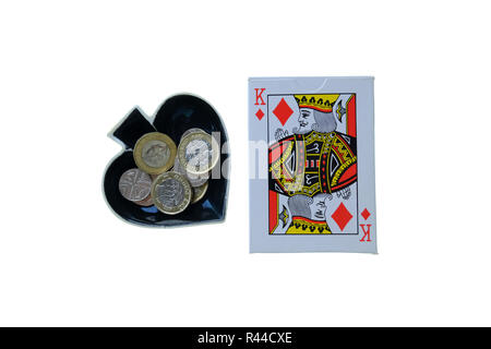 Pack of traditional playing cards on white background with Ace of Spades shaped trinket bowl to the side with loose change in it. - Stock Photo
