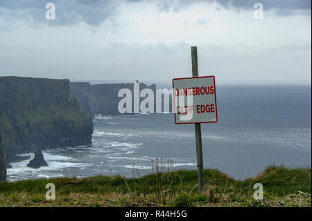 Dangerous cliff edge sign in overcast weather at Cliffs of Moher in Ireland. Danger sign warning of a vertical drop on coastal cliffs in typical irish - Stock Photo