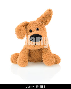 Cute dog doll isolated on white background with shadow reflection. Playful bright brown dog sitting on white underlay. - Stock Photo