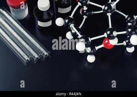molecular formula and laboratory equipment on dark background. Science organic chemistry concept - Stock Photo