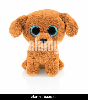 Cute dog doll with blue eyes isolated on white background with shadow reflection. Playful bright brown dog toy sitting on white underlay. - Stock Photo
