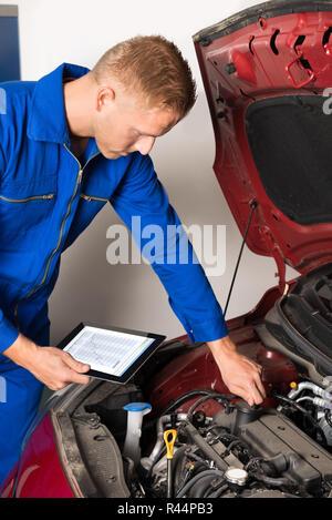Mechanic Using Digital Tablet While Examining Car Engine - Stock Photo