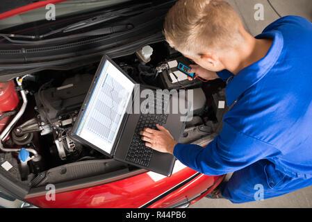 Mechanic Using Laptop To Repair Car - Stock Photo