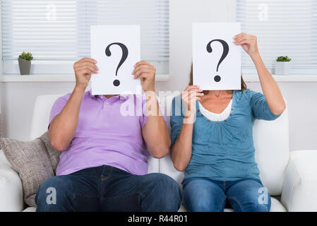 Couple Hiding Face With Question Mark Sign - Stock Photo