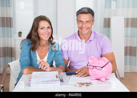 Portrait Of A Couple Calculating Bills - Stock Photo