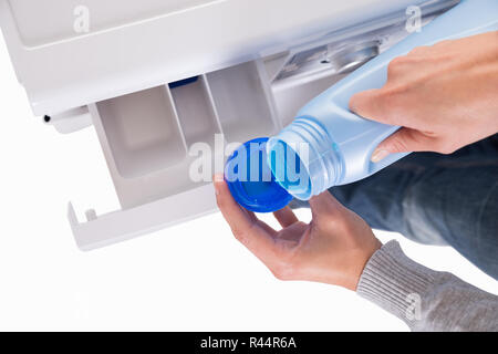 Woman Pouring Liquid Detergent In Lid For Washing Machine - Stock Photo