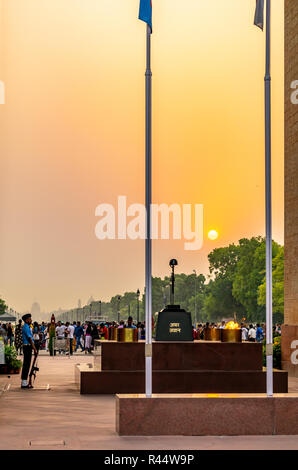 The Flame of the immortal soldier (Amar Jawan Jyoti) in the backdrop of the setting sun - Stock Photo
