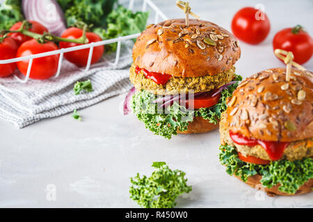 Vegan lentil burgers with kale and tomato sauce on a white background. Plant based food concept. - Stock Photo