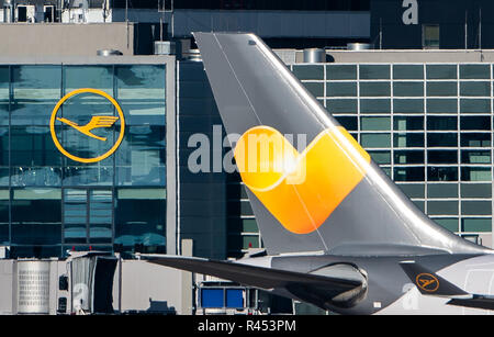 17 November 2018, Hessen, Frankfurt/Main: The logo of the airline Lufthansa (l) can be seen on a building at the airport. On the right, an Airbus A330 of the airline Condor passes the airport tarmac. Photo: Silas Stein/dpa - Stock Photo