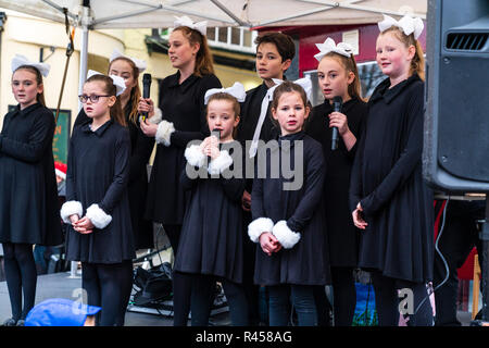 Children, girls, age 8-14 years, from the Kent Show Choir singing on outdoor stage during Christmas event at Ramsgate town. Girls dressed in black with white double bows on head. All looking at viewer. Eye-contact - Stock Photo