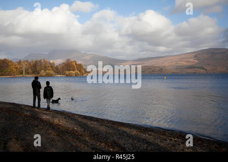 Father and son playing with dog in water with a ball at Luss on Loch Lomond, Argyll, Scotland. Ben Lomond is shrouded in cloud behind. - Stock Photo