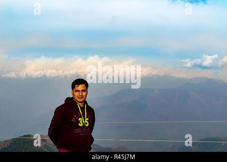 Pir Panjal Range, The Himalaya- posing after climbing to the top of the hill/ mountain, sunset sky, rays of the setting sun on the mountain range. - Stock Photo