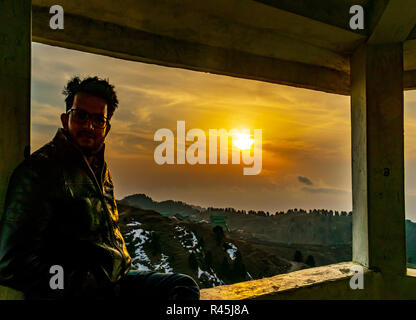 Dying embers of the setting sun- Dainkund Hills, self portrait, sunset sky in the background, from the top of the hill/ mountain, resting - Stock Photo