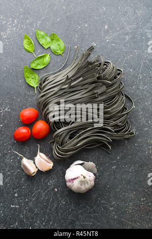 noodles, garlic, tomatoes and basil leaves - Stock Photo