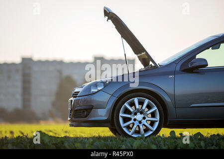 Side view detail of car with open hood on empty gravel field road on blurred apartment building and clear bright sky copy space background. Transporta - Stock Photo