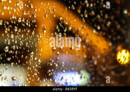 water drops on a transparent glass surface with blurred bokeh background - Stock Photo