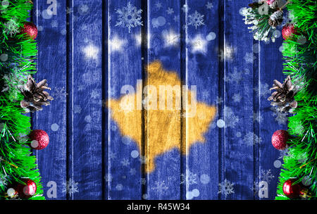 Wooden Christmas background with blurred flag of Kosovo. There is a place for your text in the photo. - Stock Photo