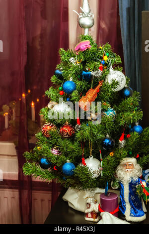 Christmas tree decorated with multicolored Christmas toys and Santa Claus against the background of a window with burning Christmas candles. - Stock Photo