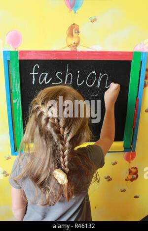 girl with nice plaits writes Fashion on blackboard - Stock Photo