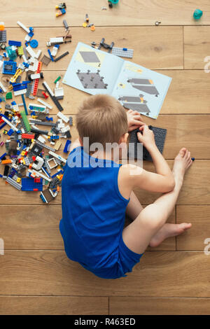 Overhead shot of boy playing with Lego bricks - Stock Photo