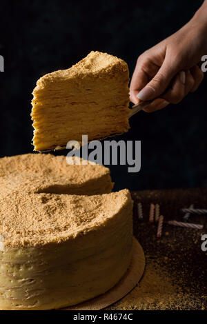 A piece of traditional napoleon cake. Still life in dark colors - Stock Photo