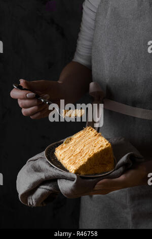 Woman holding a piece traditional napoleon cake. Still life in dark colors - Stock Photo