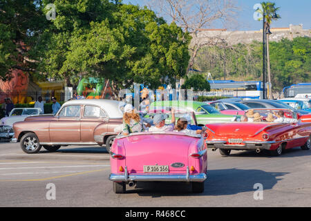 Tourists take the opportunity to ride in a vintage American car in downtown Havana Cuba. - Stock Photo
