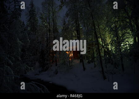 House with light in window among night, snowy winter forest, Finland - Stock Photo