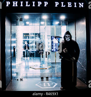 Person dressed up as the grim reaper in front of a Philipp Plein retail shop in San Babila, Milan, Lombardy, Italy ahead of the festive season - Stock Photo