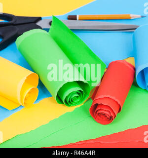 rolled color paper on sheets of plain paper - Stock Photo