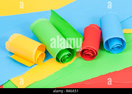 rolled colour paper on sheets of torn paper - Stock Photo