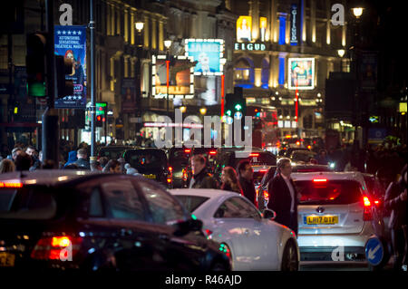 LONDON - DECEMBER 23, 2018: Pedestrians cross a traffic-clogged intersection at Piccadilly Circus in front of the shining lights of West End theatres. - Stock Photo