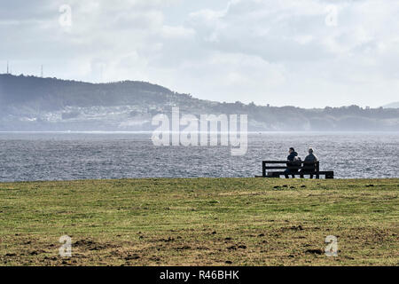 Two men sitting on a park bench Hercules sculptural garden contemplating the seascape of the atlantic ocean in Galicia, Spain - Stock Photo