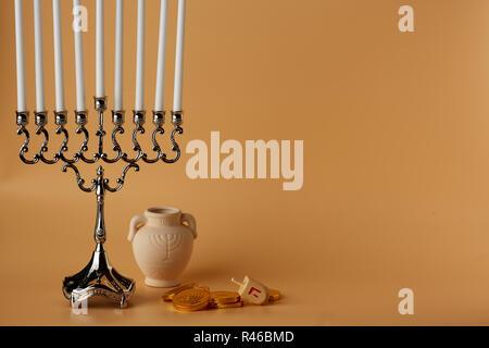 Image of jewish holiday Hanukkah with menorah and wooden dreidel, jug, coins - Stock Photo