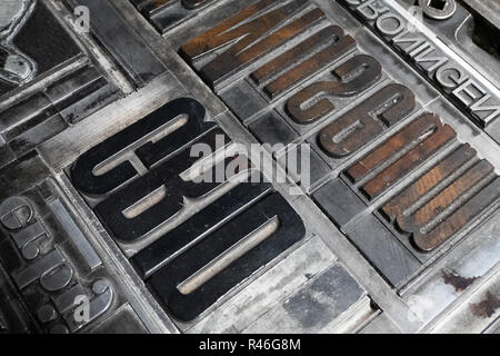 Close up of inverted metal type letters for setting on an old  Heidelberg printing press. - Stock Photo