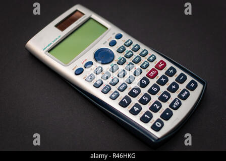 Close up of a calculator laying on black background - Stock Photo