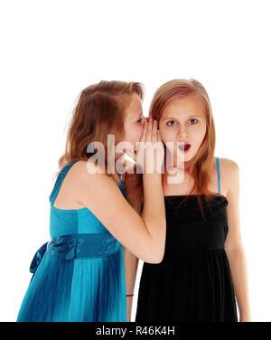 Two girls sharing secrets. - Stock Photo