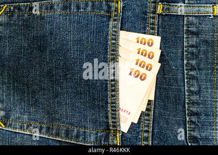 Thai bank note in jeans pocket - Stock Photo