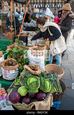 A female customer shopping for vegetables at the Farmer's Market on Castle Terrace, Edinburgh, Scotland, UK. - Stock Photo