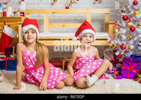 Funny girl gnome sitting on a mat in a Christmas setting - Stock Photo