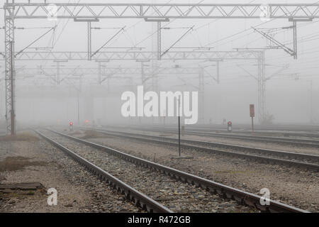 Old train wagons parked in the morning mist - Stock Photo