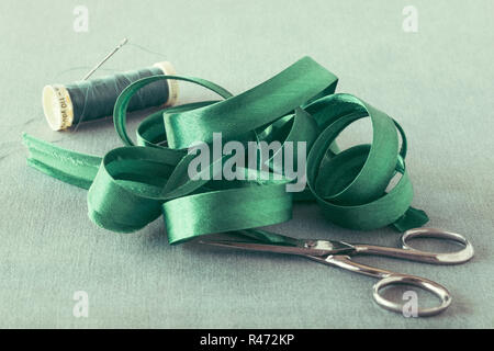 Green satin Bias binding close up with scissors and thread - Stock Photo