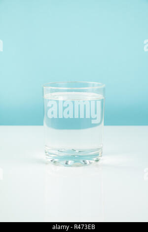 Glass with water on a table. Hunger or diet concept: clean transparrent drink in white and blue background - Stock Photo